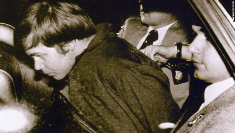 WASHINGTON, UNITED STATES: This 30 March 1981 file photo shows John Hinckley Jr. (L) escorted by police in Washington, DC, following his arrest after shooting and seriously wounding then US president Ronald Reagan. A federal judge ruled 17 December 2003 Hinckley can make local visits with his family from St. Elizabeth's Hospital in Washington, DC, where he has been held. AFP PHOTO/FILES (Photo credit should read AFP/AFP/Getty Images)