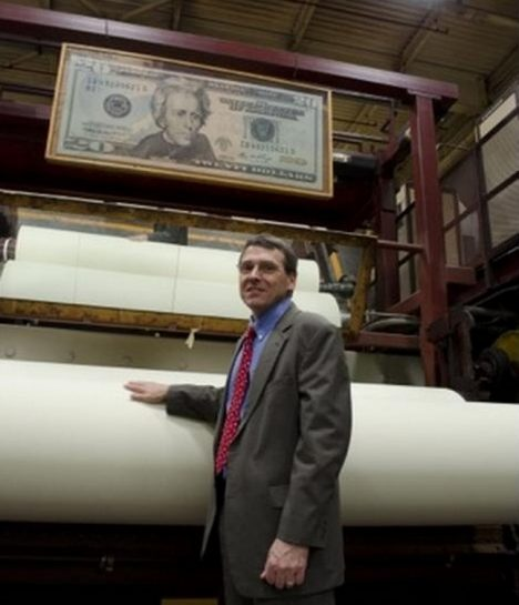 Crane & Co. Vice President Doug Crane stands near a spool of paper used for $20 bills, as it spins at the company's Wahconah Mill. Robert Benincasa/NPR