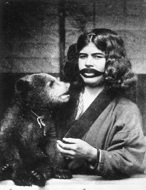 Ainská žena chová medvěda se stejnou láskou jako vlastní dítě.