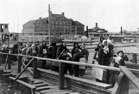 : Immigrants including the Bombardelli family from Italy, entering the United States through Ellis Island, the main immigrant entry facility of the United States from 1892 to 1954. The large building is the original hospital building (still there 2014; there are now two more to its left) seen from across the ferry slip. The people must be walking on some sort of pier from a ferry or launch toward the Main Building.