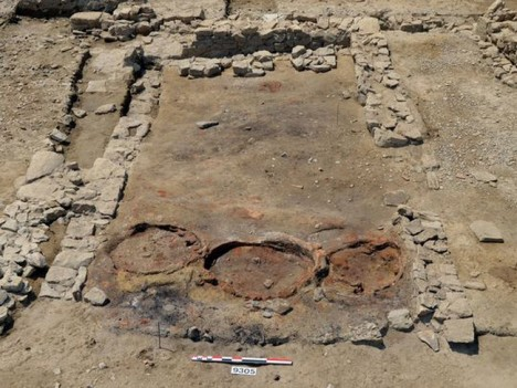 The kitchen of what looks like an ancient tavern, with three reddish circles where the three ovens -- for baking flatbread and other dishes -- once stood. (Photo: Lattes excavations)