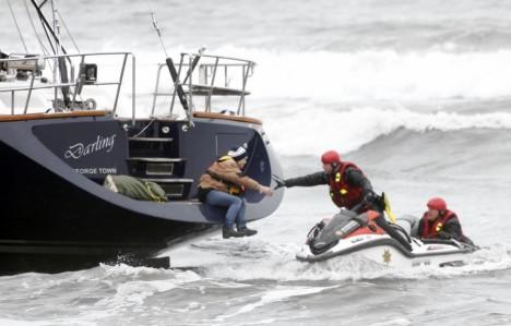 Pasažéry uvízlé lodi zachraňují policisté na vodních skútrech.