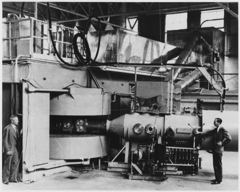 Lawrence's 60-inch cyclotron, with magnet poles 60 inches (5 feet, 1.5 meters) in diameter, at the University of California Lawrence Radiation Laboratory, Berkeley, in August, 1939, the most powerful accelerator in the world at the time. Glenn T. Seaborg and Edwin M. McMillan (right) used it to discover plutonium, neptunium and many other transuranic elements and isotopes, for which they received the 1951 Nobel Prize in chemistry. The cyclotron's huge magnet is at left, with the flat accelerating chamber between its poles in the center. The beamline which analyzed the particles is at right.