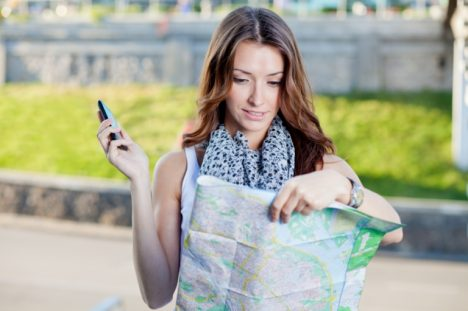 young woman tourist holding paper map outdoors and talking by the phone