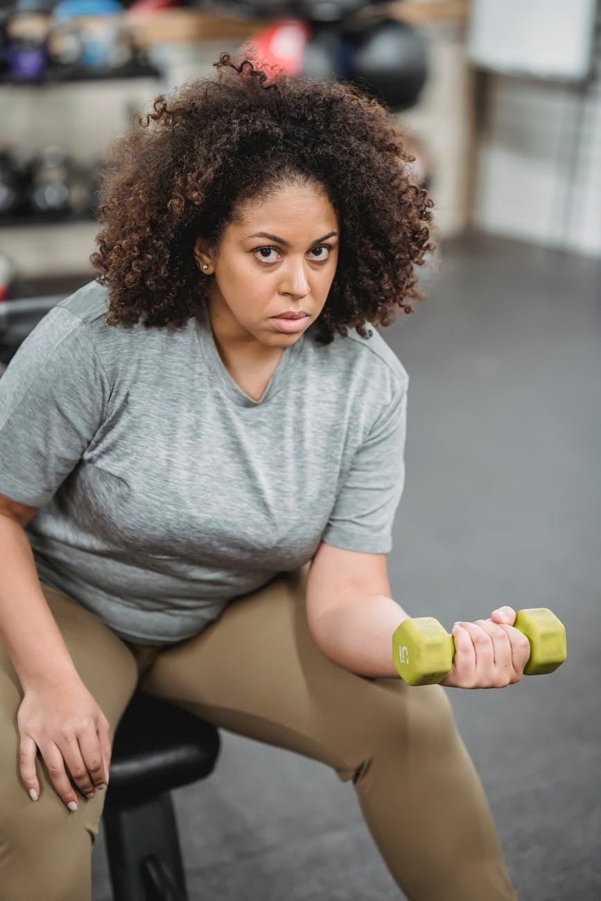 overweight black woman exercising with dumbbell in gym