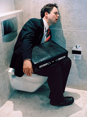 Businessman sleeping on toilet