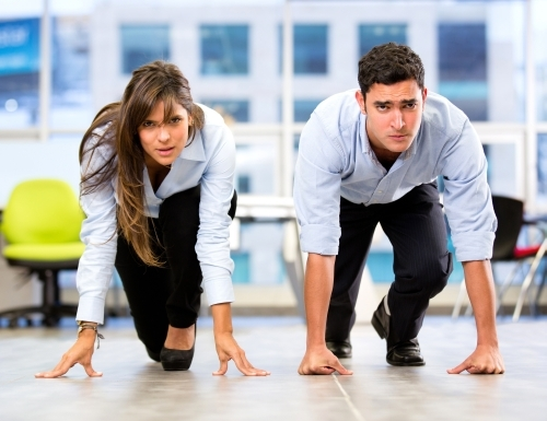 Competitive business couple racing at the office