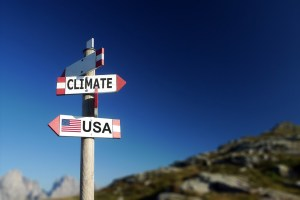 Climate change and American flag in two directions on road sign. Withdrawal of climatic agreement.