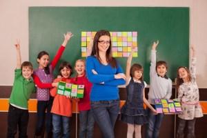 Children in elementary school posing with their teacher in front of chalkboard