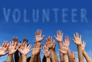 volunteer group raising hands against blue sky background