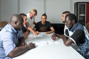 Language training for refugees in a German camp: A female German volunteer is teaching young African (Gambia) and Arabic (Algeria and Tunesia) men the German language in a refugee camp quickly errected using accomodation containers. Over 1 million refugees arrived in Germany in 2015 alone, integration of these people requires enormous efforts by the government but also by thousands of volunteers providing basic training and services for the refugees.