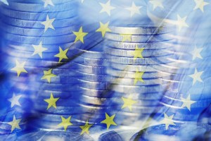 a multiple exposure of some piles of euro coins and a flag of the European Union