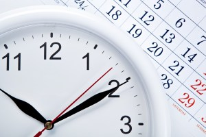 clock face and calendar sheet with numbers closeup