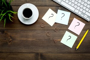 Question mark on sticky notes on office desk on dark wooden background top view. FAQ concept. Working with clients. Troubles in work