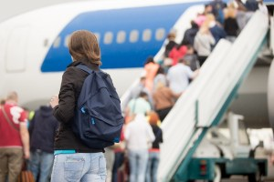 Girl boarding plane, back view