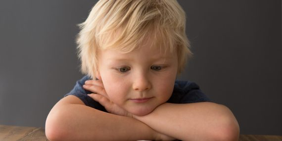 A young blond child leaning on their crossed arms on a table, staring at a marshmallow.