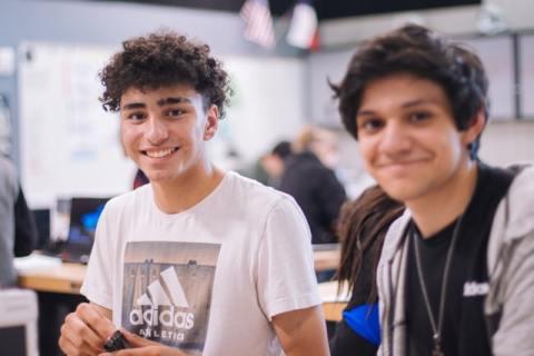 Two teenage boys in school, smiling