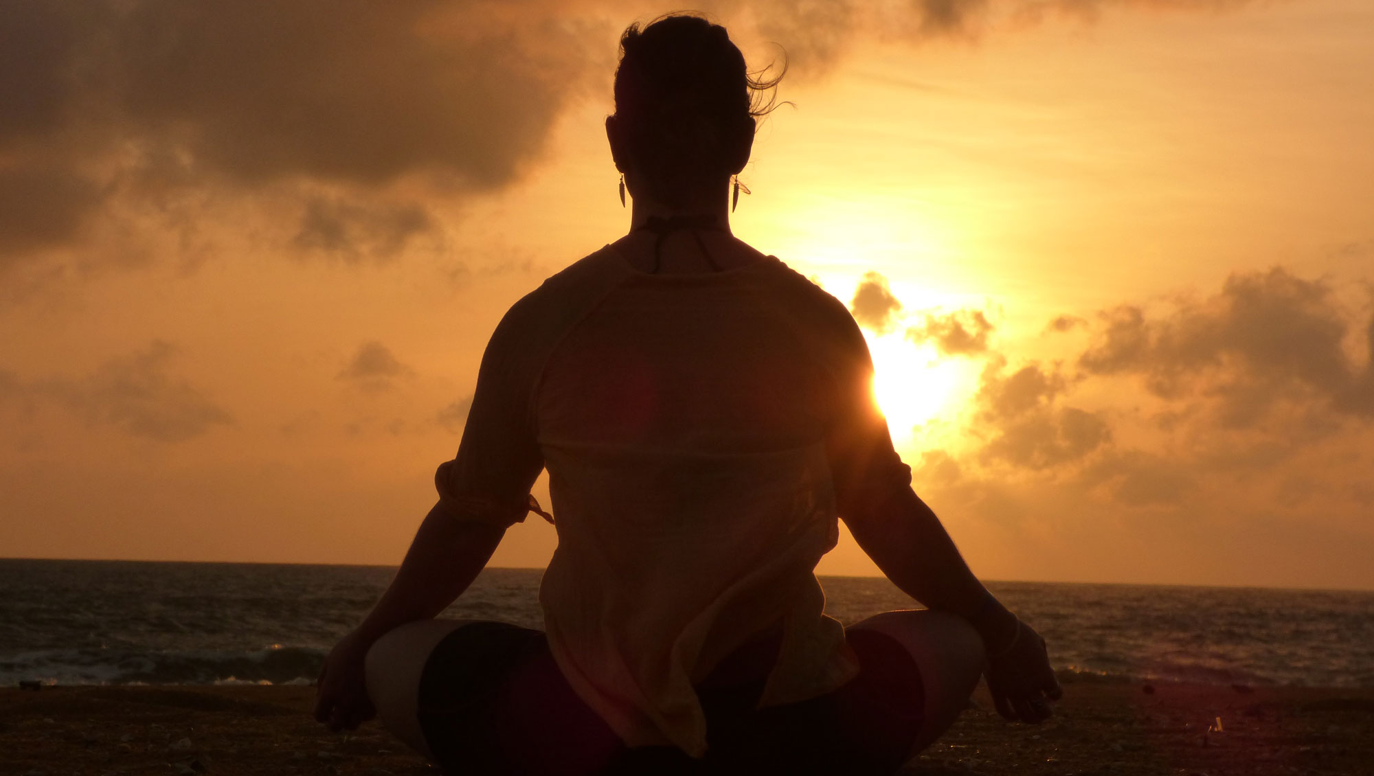 Equanimity Yoga meditating on a beach at sunset