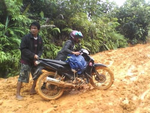 Akses Buruk. Pengendara motor terpaksa mendorong kendaraannya saat melintasi jalan menuju Desa Langan. Sukartaji/RK