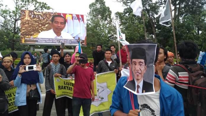 CATATAN UNTUK JOKOWI. Mahasiswi-mahasiswi ini tengah menujukkan kalimat-kalimat penolakan kenaikan BBM yang tertulis di karton dalam aksi damai di Taman Digulis Untan Pontianak, Jumat (30/3) sore. Saat karton itu diangkat, Jokowi tampak sedang 'menatapi' aksi itu dalam sebuah videotron iklan di lokasi aksi—Ocsya Ade CP