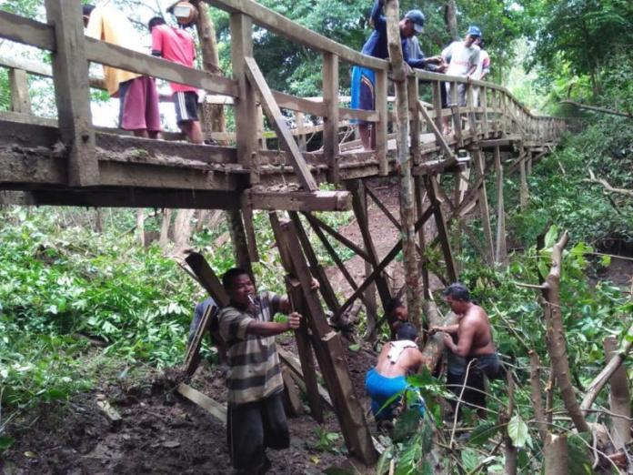 Jembatan Rusak. Warga berjibaku melakukan perbaikan sementara agar jembatan Sungai Kempas tetap bisa dilalui warga, Kamis (28/6). Handika for Rakyat Kalbar