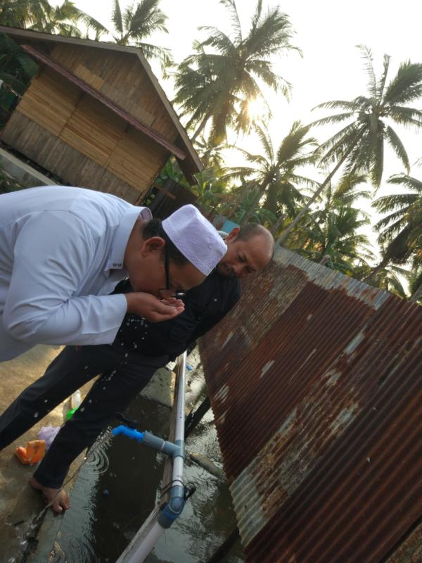 AIR BERSIH. Dosen FT Untan, Eka Priadi (kemeja hitam), bersama pimpinan Pondok Pesantren As-Shiddiqiyyah, Desa Sungai Itik, Kecamatan Sungai Kakap, Kubu Raya, mencoba air bersih yang dihasilkan instalasi yang dibangun FT Untan. FT for RK