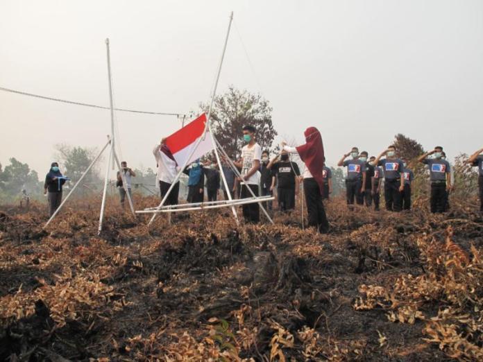EKS KARHUTLA. MASKERAN memperingati HUT ke 73 RI dengan menggelar pengibaran bendera merah putih di lahan eks kebakaran lahan Jalan Sepakat II Ujung, Jumat (17/8). Maulidi Murni-RK