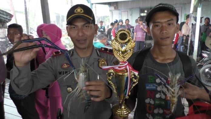 UDANG TERBERAT. Kapolsek Sejangkung, Ipda Wismo Harjanto bersama Juara Lomba Mancing Udang HUT Bhayangkara ke-72, M Kholir yang berhasil mendapatkan udang seberat 3,1 ons, Minggu (29/7). Sairi