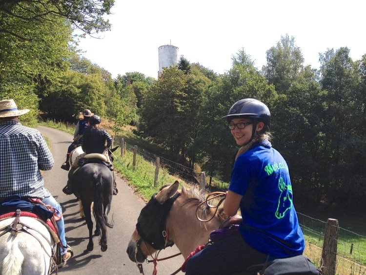 A group of mule riders approaching a castle up the hill in Germany