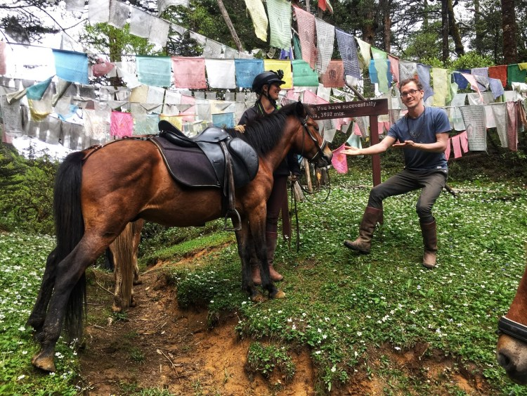 Krystal her husband and the Bhutanese mountain pony Firefly are happy to have reached the highest point of the Febila pass, Bhutan