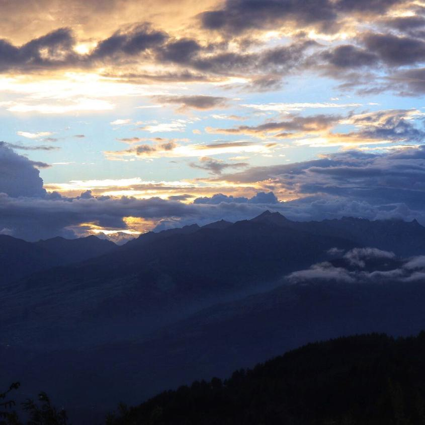 The sun sets behind some clouds over the Himalayan mountain range