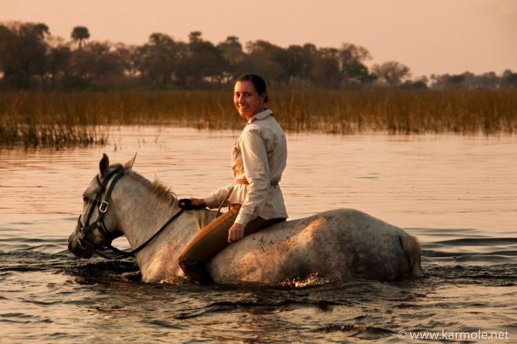 Aga Karmol crossing a river bareback in the Okavango Delta, Botswana.