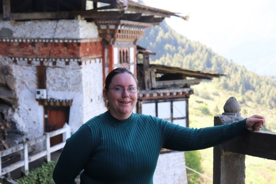 Amber in front of a temple in Bhutan, smiling and happy to have chosen this country for her first time international travel