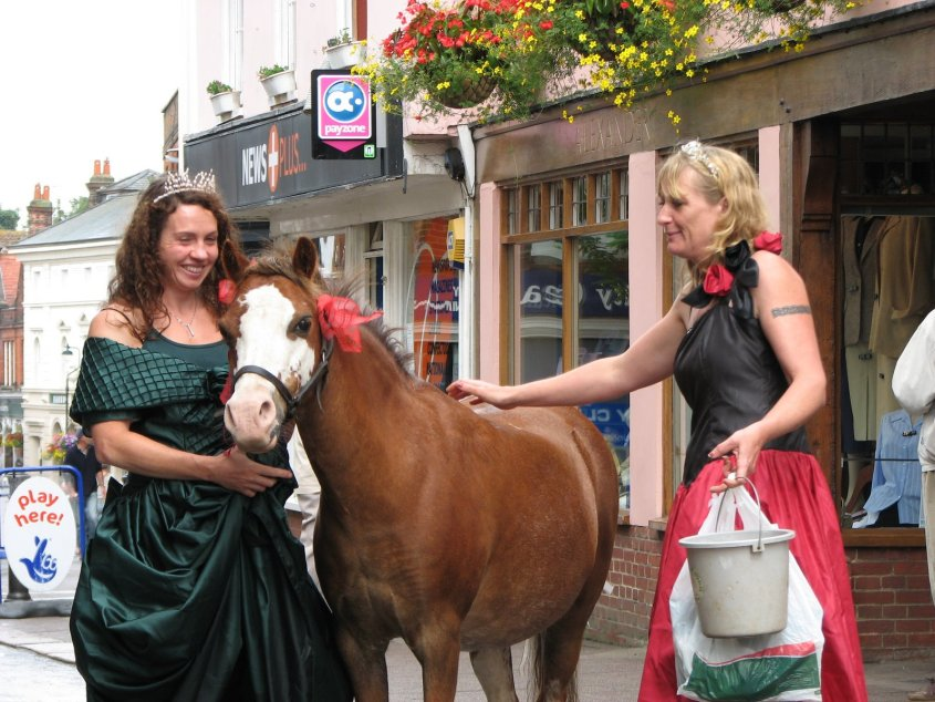 Tess and Michele in their ballroom dresses in a small town with a pony