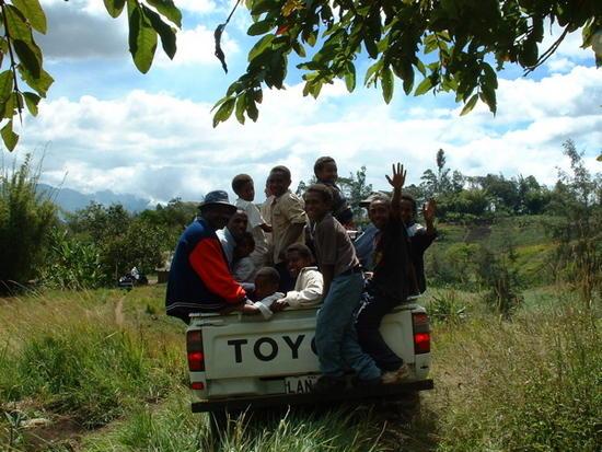 men riding around in a truck in papua new guinea