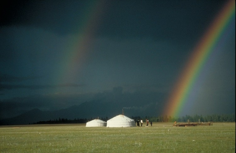 Mongolian grassland with two gers under a double rainbow
