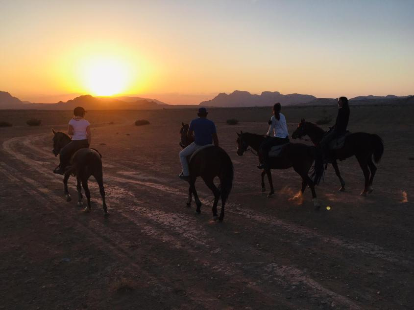 Four riders walking into a spectacular sunset while horse riding in Jordan.
