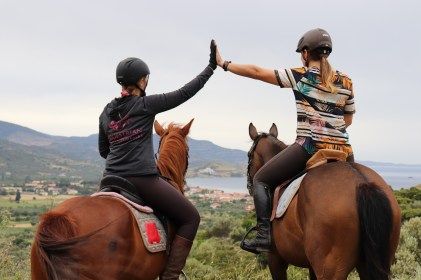 Two Equestrian Adventuresses giving a high five on horseback looking into the distance on a Greek island