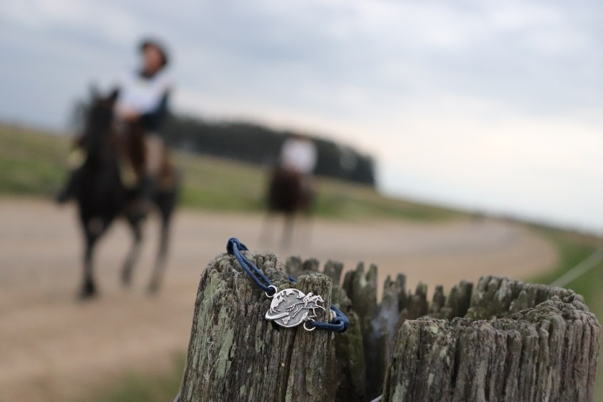 This Sterling Silver Equestrian Jewelry piece is presented on a wooden post with competing riders in the background