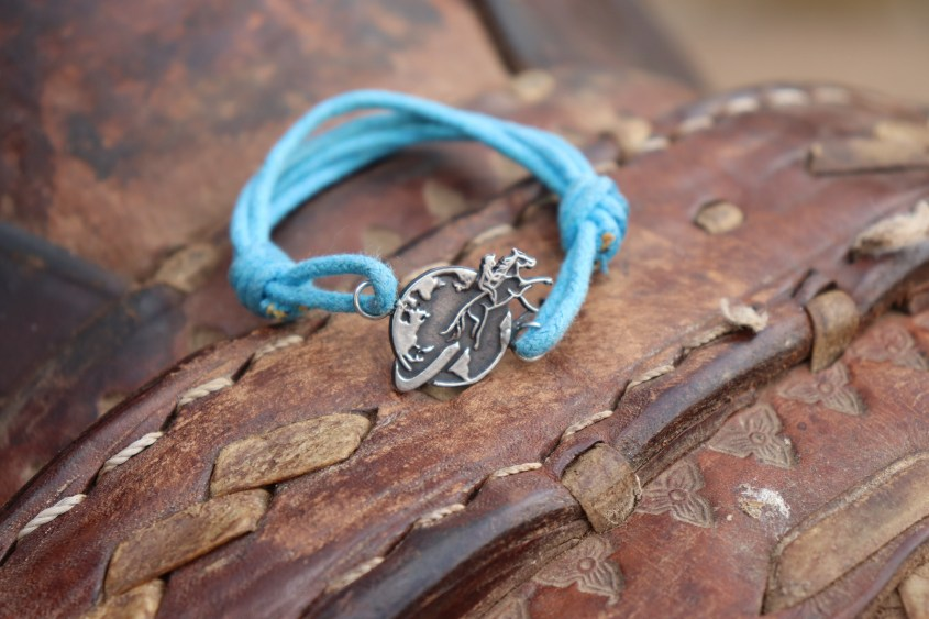 The Lighting Blue Bracelet resting on a traditional leather saddle