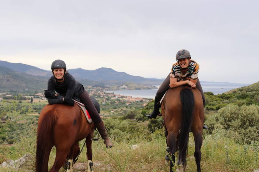 Two adventurous women have fun during a break of riding horses in Greece. While the horses face towards the town of Petra on Lesvos, the women sit backwards in the saddle resting their arms on the horses hips.