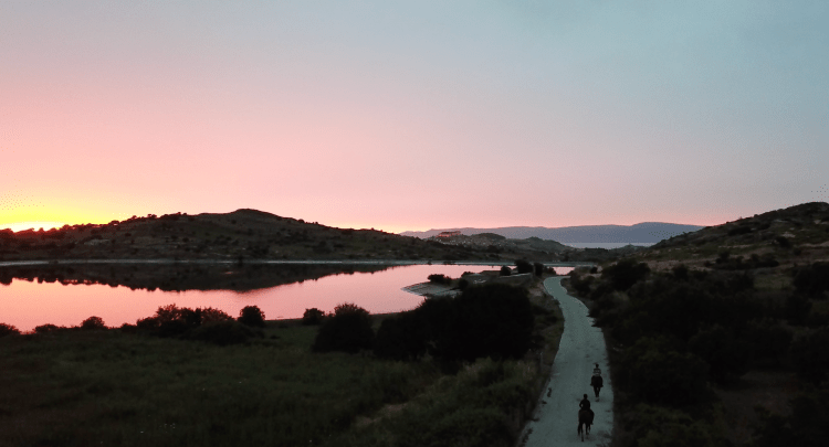 Two people are riding horses in Greece along a lake towards Molyvos during the sunset. The sky and the lake shine in bright pink and red color.