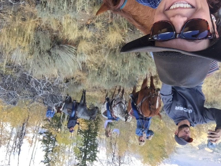 a group of riders taking selfies while horse riding in Colorado