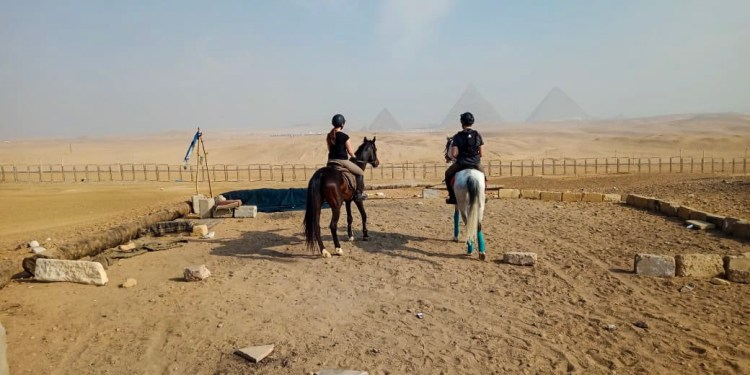 Two riders are looking at the pyramids in Giza during a horse riding excursion in Egypt