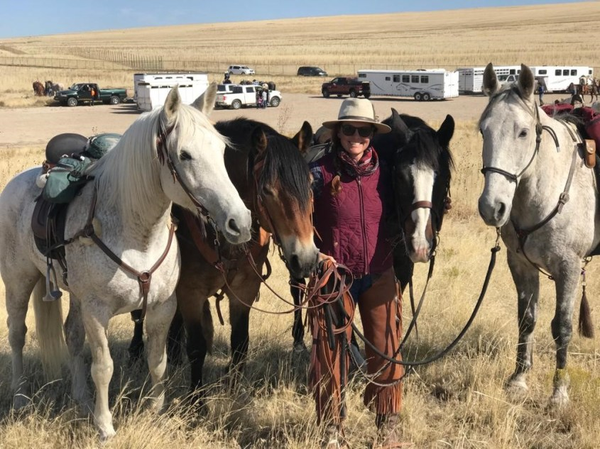 Adrienne holding the 4 horses she and her friends would use in their upcoming equestrian adventure of rounding up bison on Antelope Island, Utah
