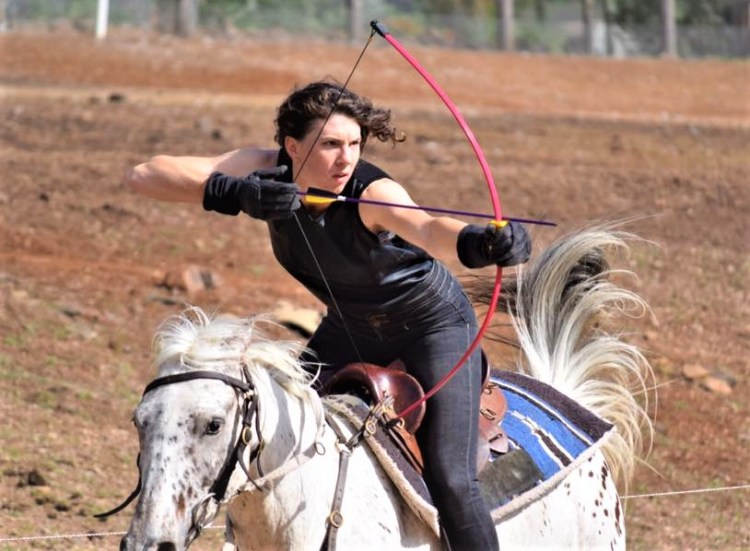 Odessa is practising horse archery on a mare to improve her horsemanship in Australia