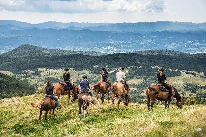 Horse riders in Slovenia look over the land from a mountain top in Slovenia