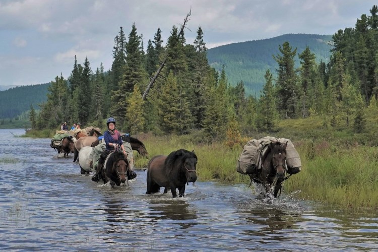 Guests ride alongside the pack horses at the shore of a lake in Mongolia