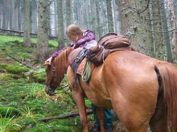 Sarah and Alazana catching their breath. Sarah is standing beside her horse in a forest
