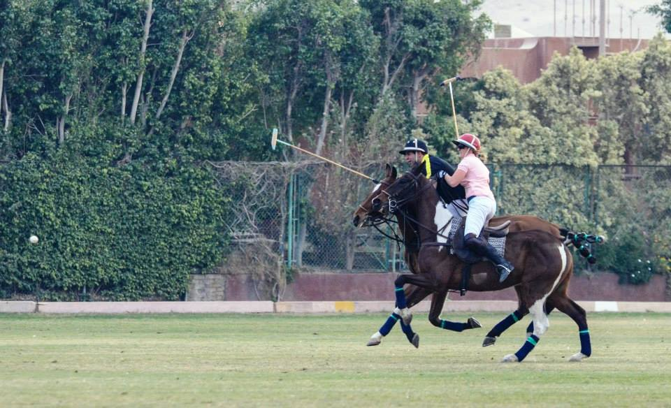 Two riders galloping next to each other playing polo